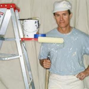 Målare bredvid en nymålad vägg